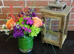 A lovely purple, orange and green arrangement, offset by an antique lantern